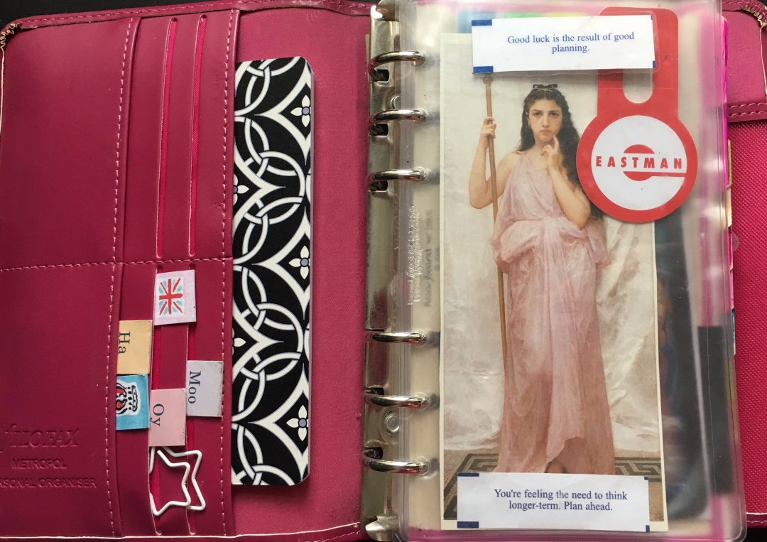 Inside a Filofax with sticky notes and postcards and fortunes