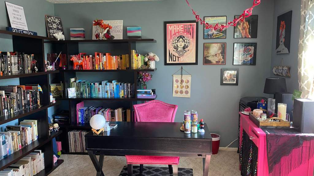 A view of the author's office space with books arranged by color, a cleared desk, and various decorations on the wall